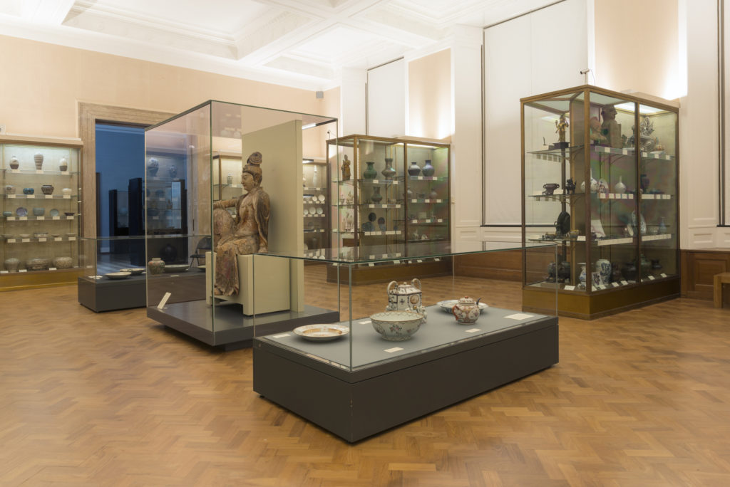 photograph of pots and statue in a museum gallery