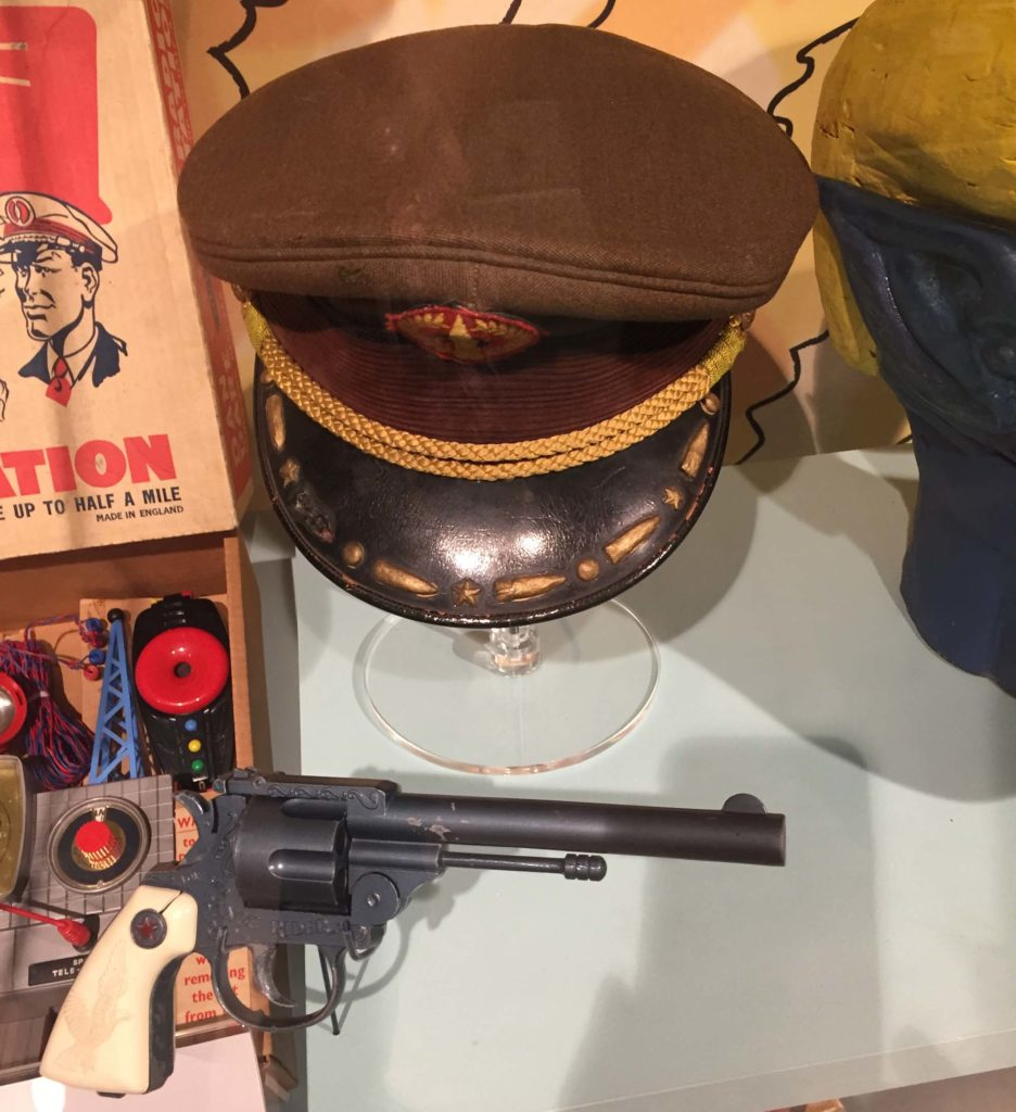 a photo of a Dan Dare militray hat and revolver in a display case