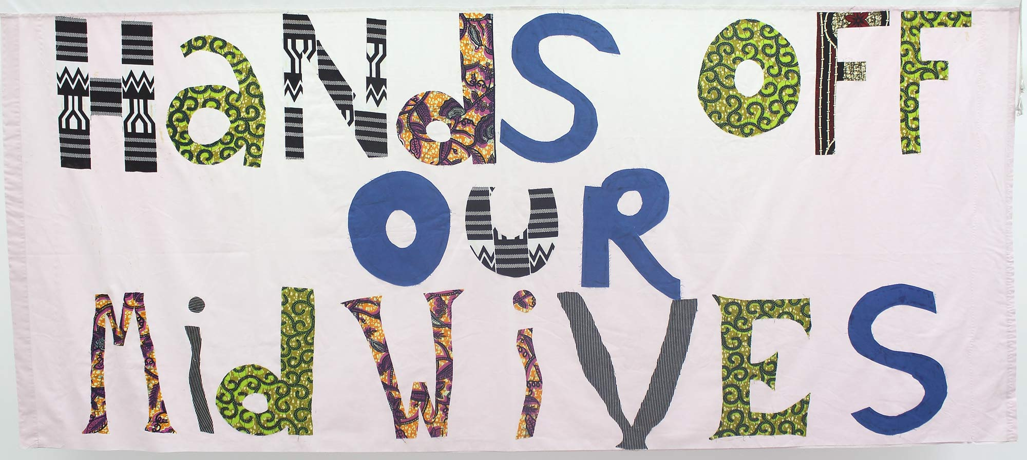 a bedsheet banner with the words hands of our midwives appliqued in colourful fabric