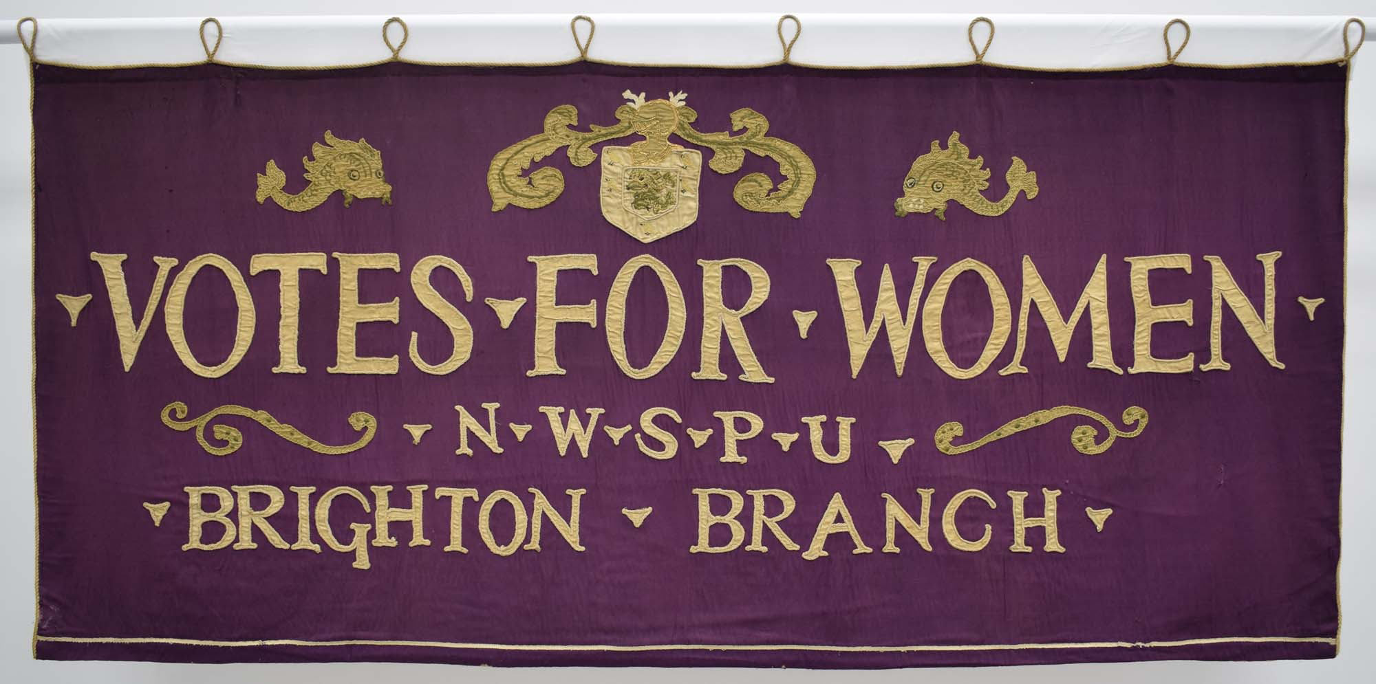 a purple votes for women banner with Brightoon NWSPU Brighton Branch written on it