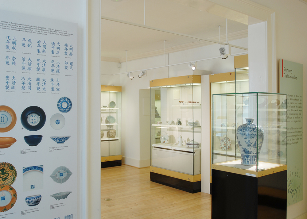Photograph of entrance to museum gallery showing Chinese ceramic vase in display case, next to an information board about Chinese lettering