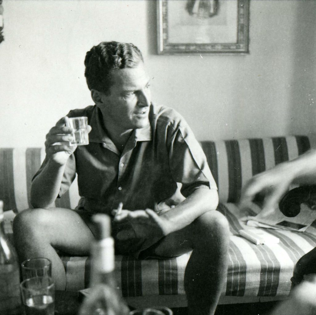 a photo of a seated man in shorts smiling and smoking a cigarette