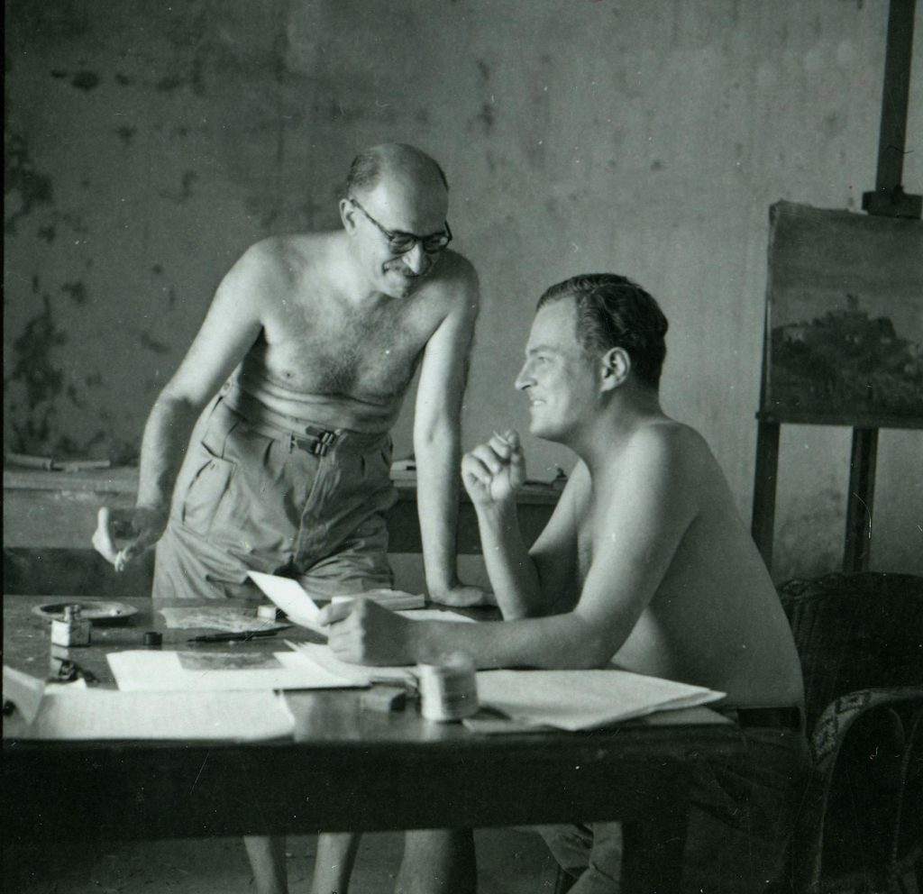 a photo of two men with tops off discussing somethig around a desk