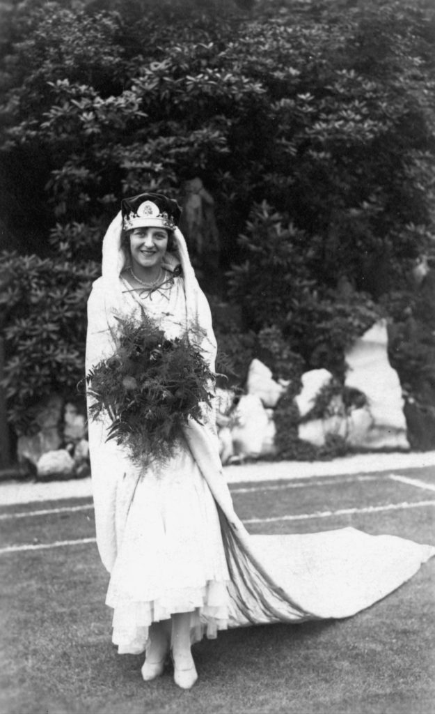 a photo of a woman in a regal white dress with a train, wearing a crown and carrying a bouquet
