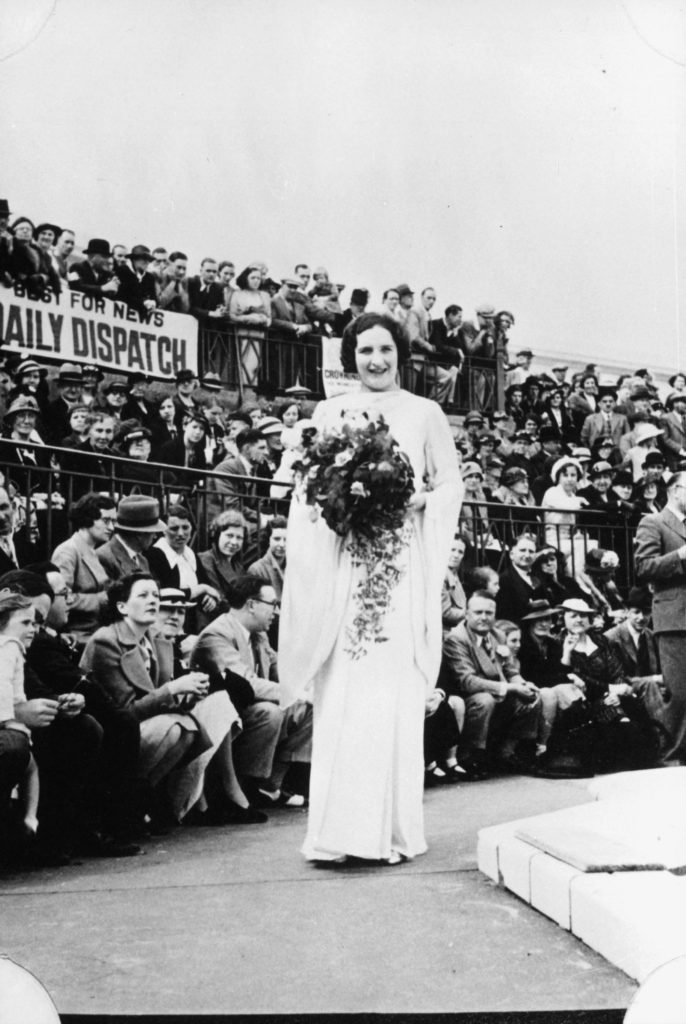 a photo of a woman in a white dress carrying a bouget around a catwalk watched by crowds outside