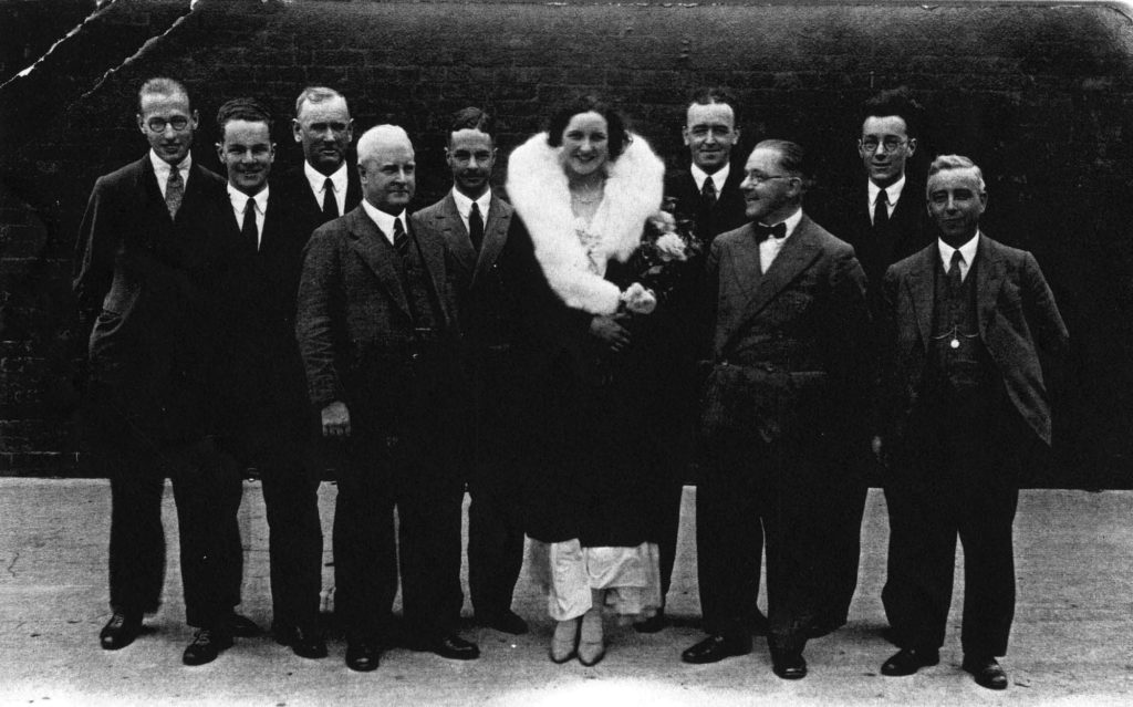 a photo of a woman in a fancy dress and coat flanked by men wearing suits and ties