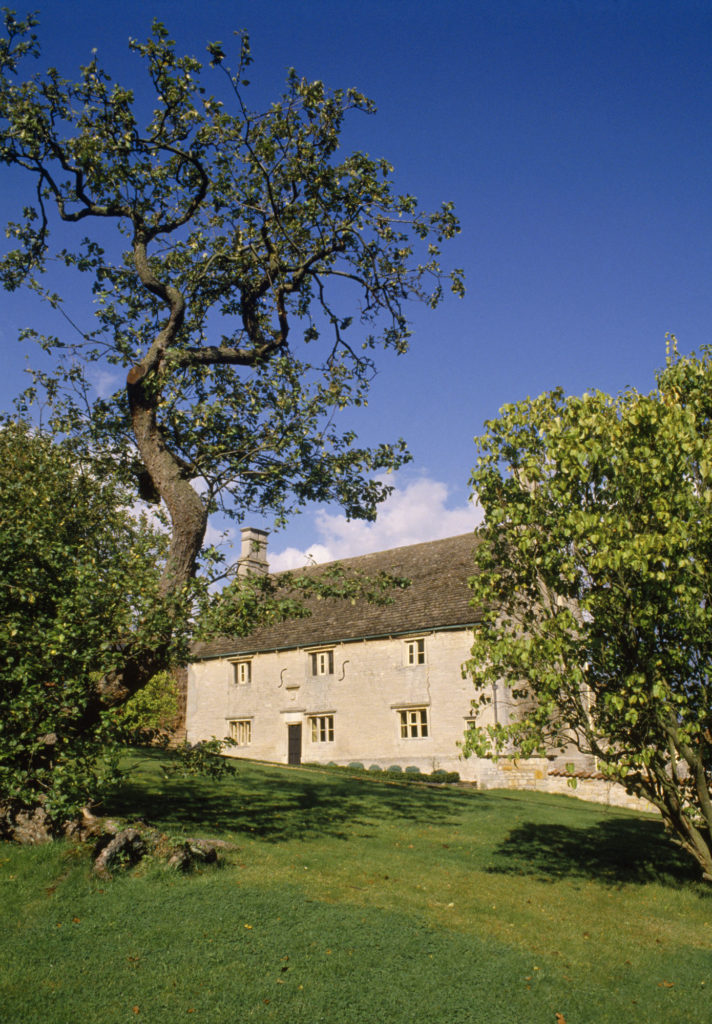 photograph of grey-bricked house with apple tree outside