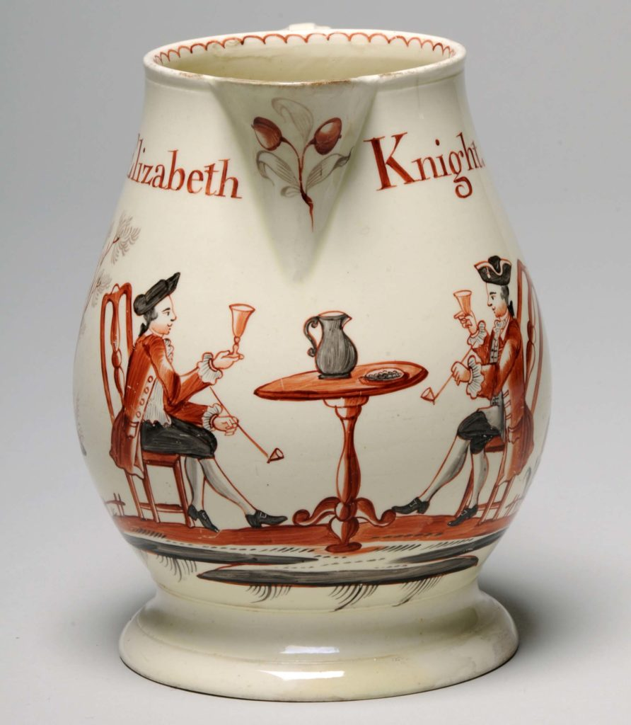 A photo of a jug decorated with beer drinkers
