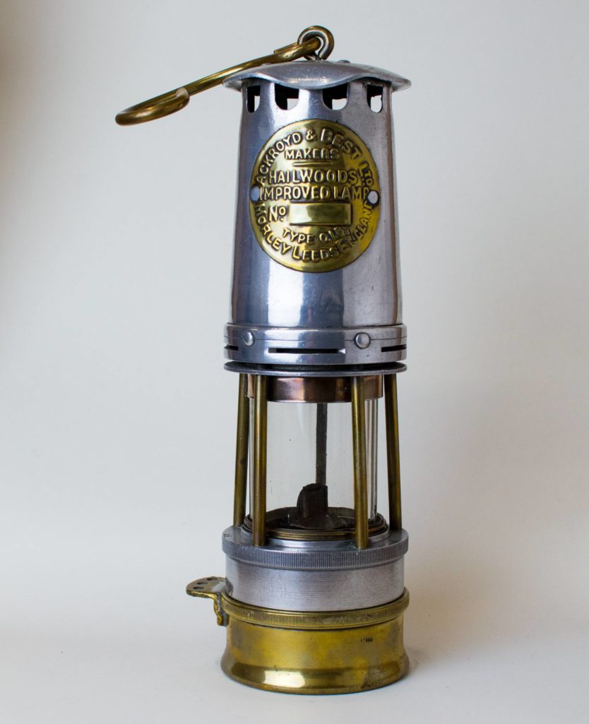 a photo of a steel lamp with glass chamber and brass base