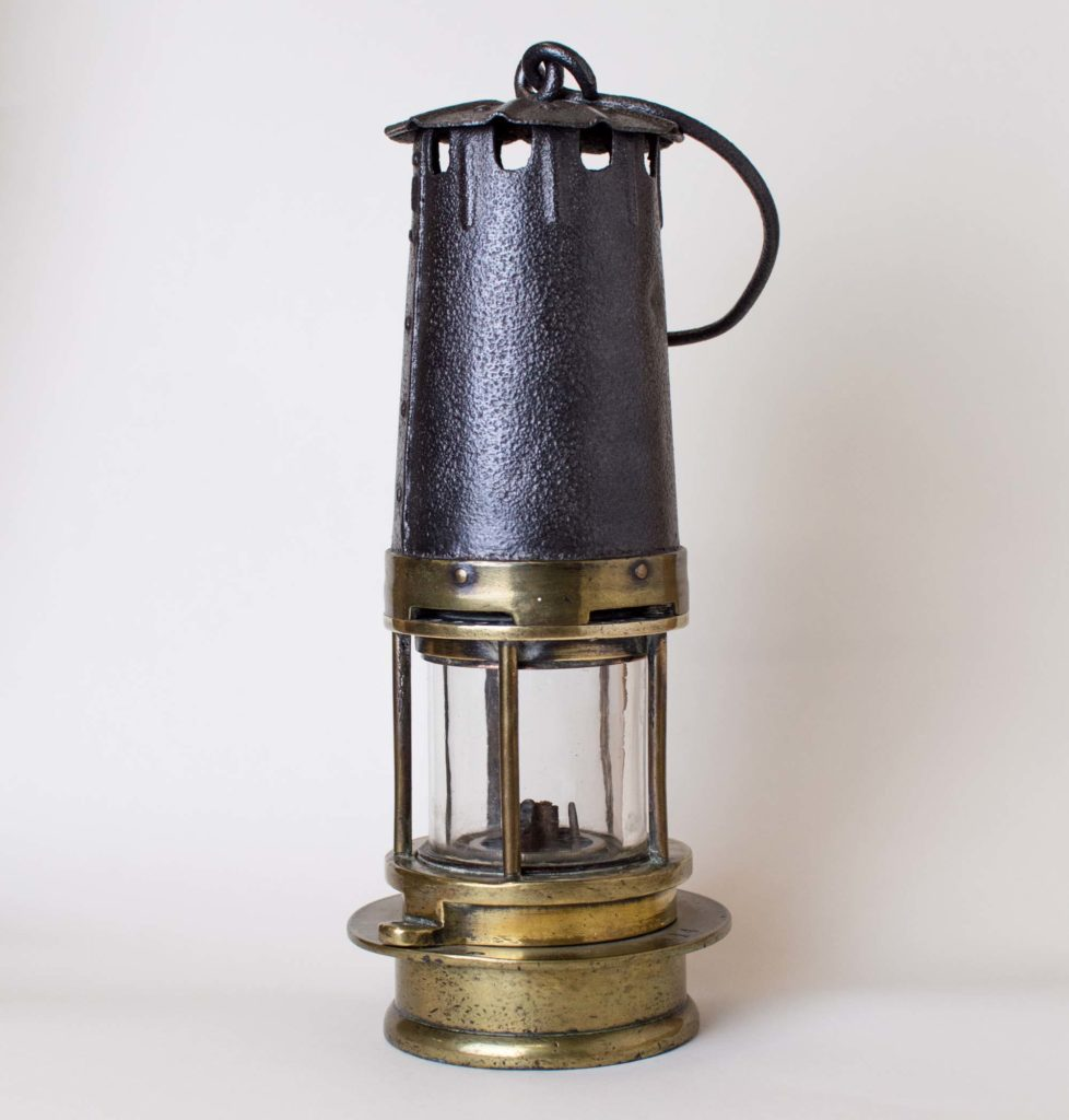 a photo of a miners lamp with brass bottom, glass chamber and steel upper body