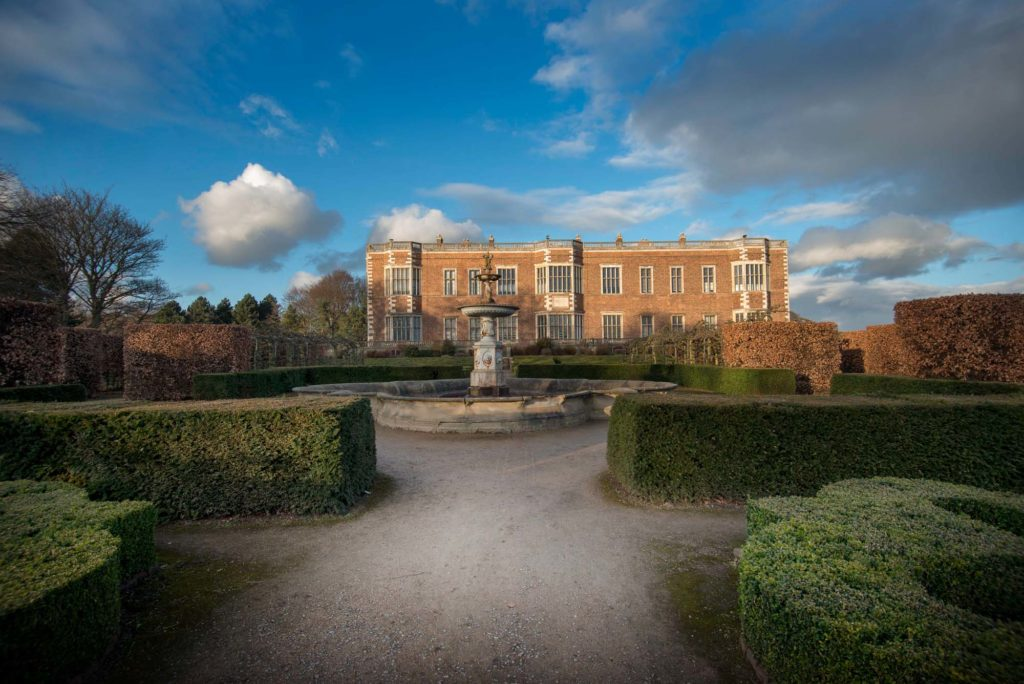 a photo of a large country house in gardens