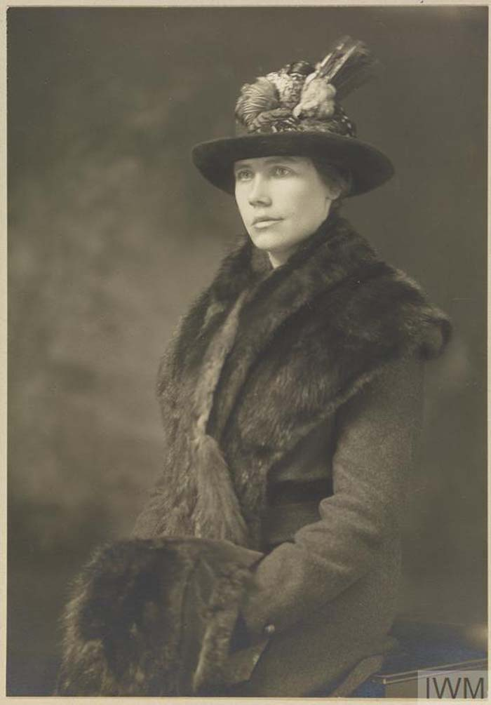 a black and white portrait of a Lady in hat, coat and muffler