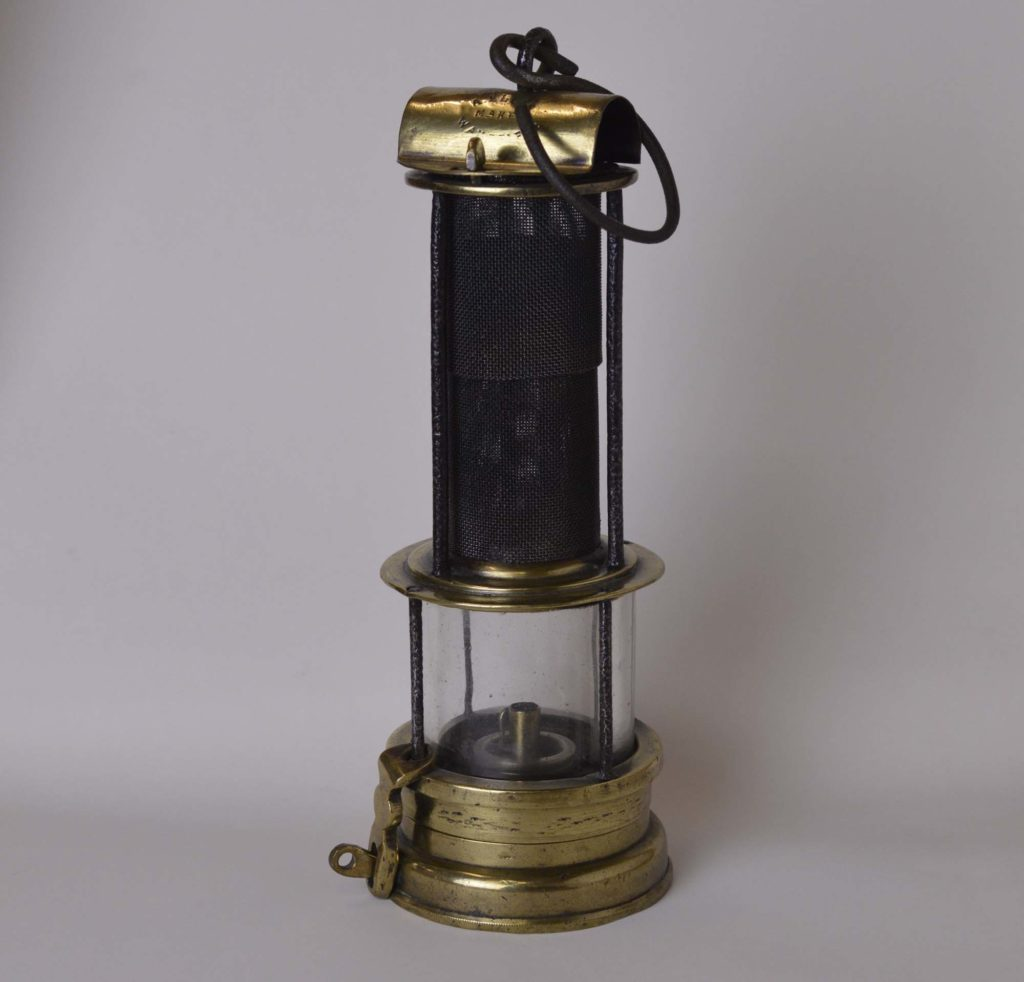 a photo of a lamp with brass to and base beneath a circular brass chamber