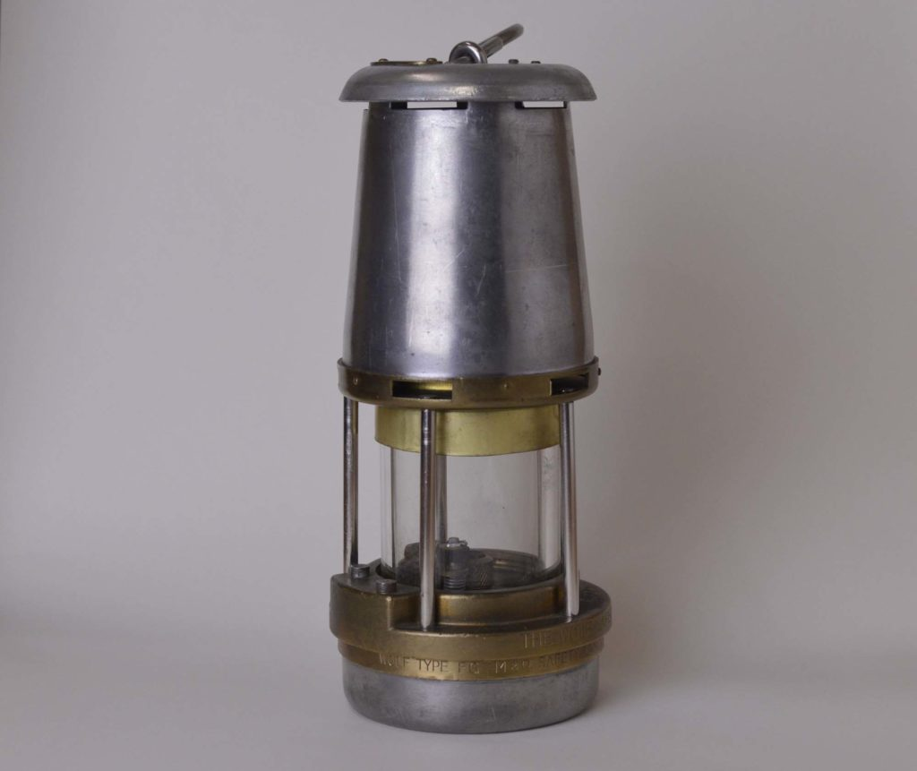 a photo of a small steel lamp with glass chamber inlaid with brass supports