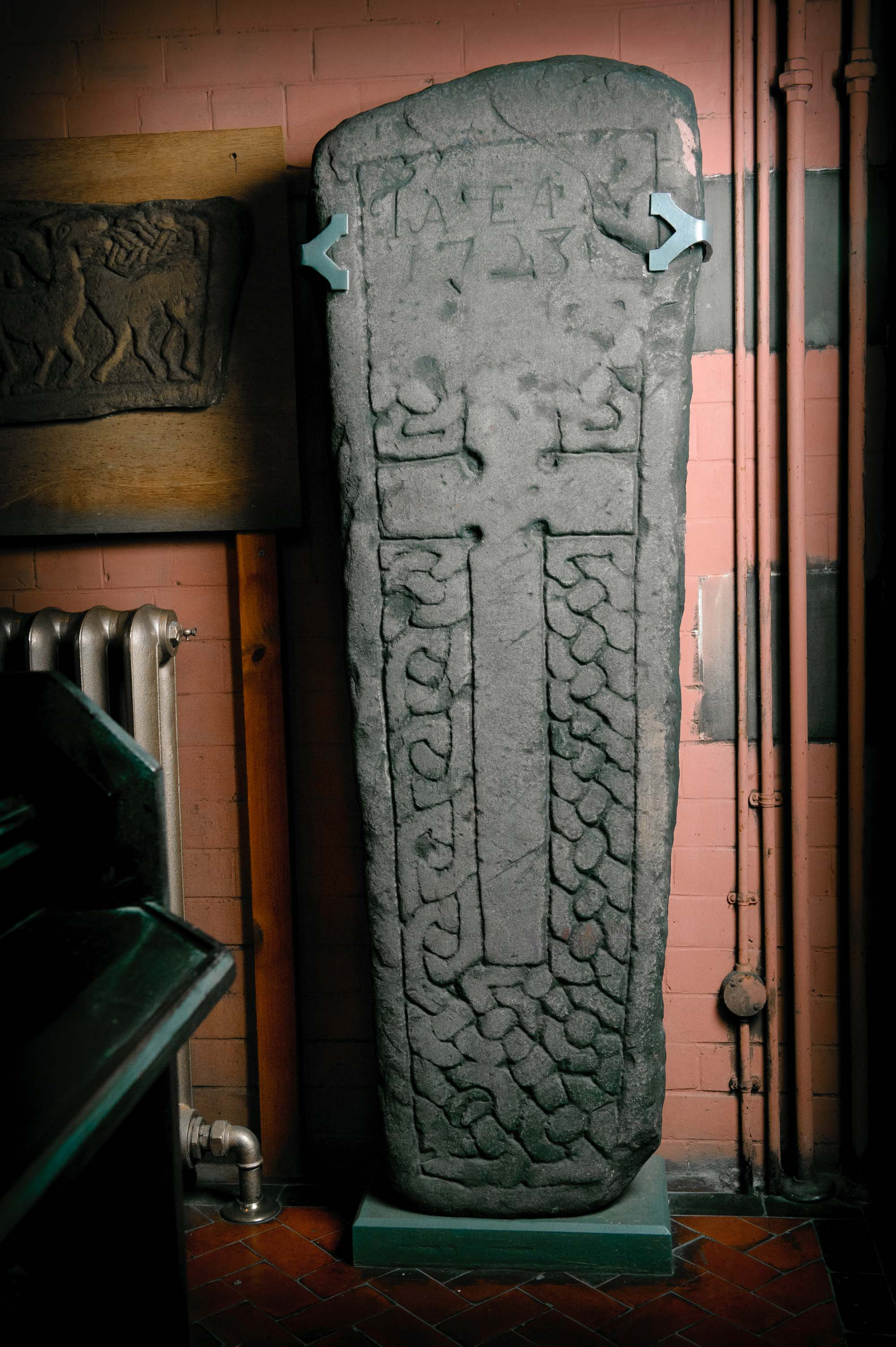 a photo of a stone slab with crucifix and Celtic decoation attached to a Church wall
