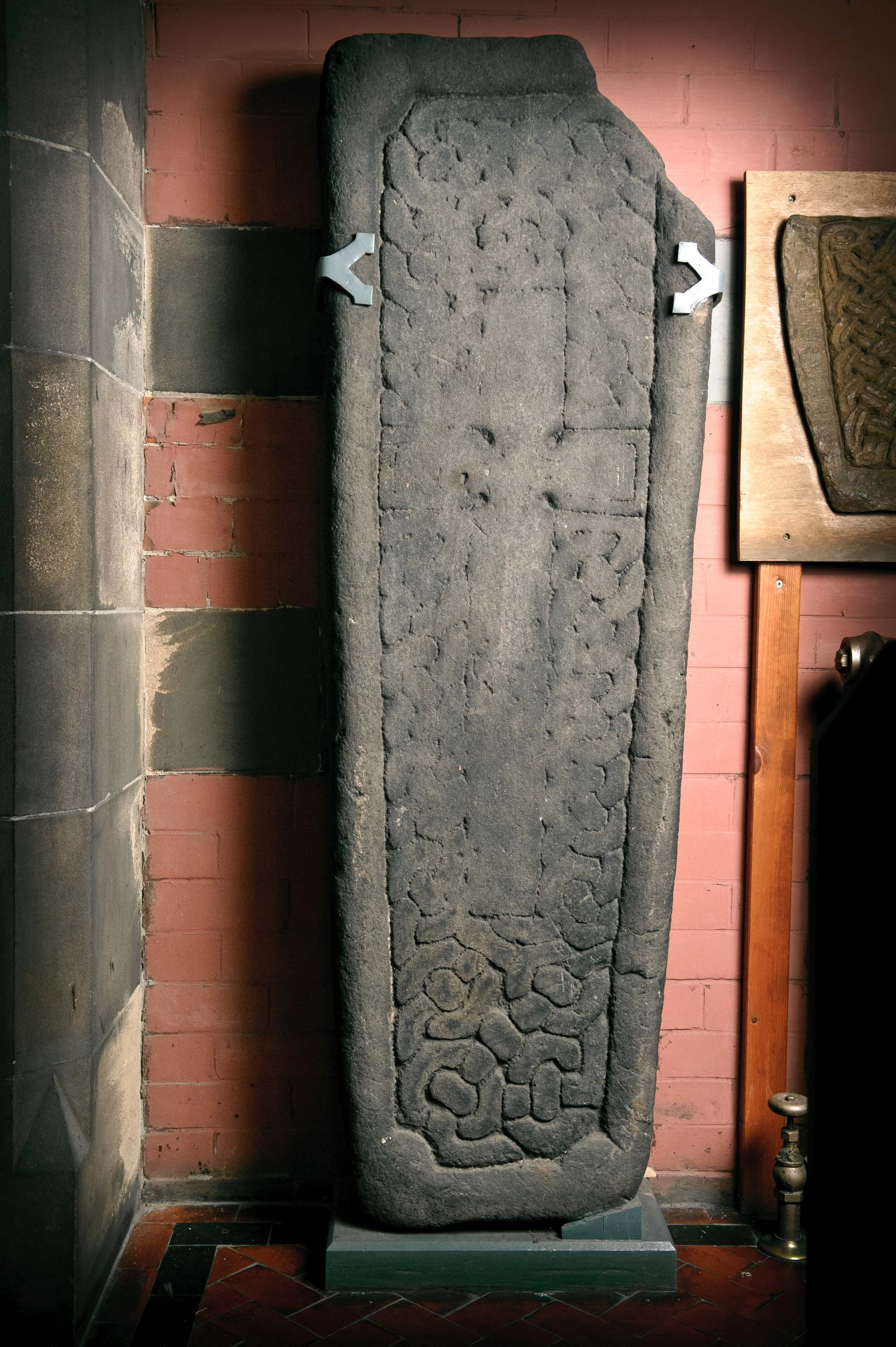 a photo of a stone slab decorated with Celtic carvings and a crucifix