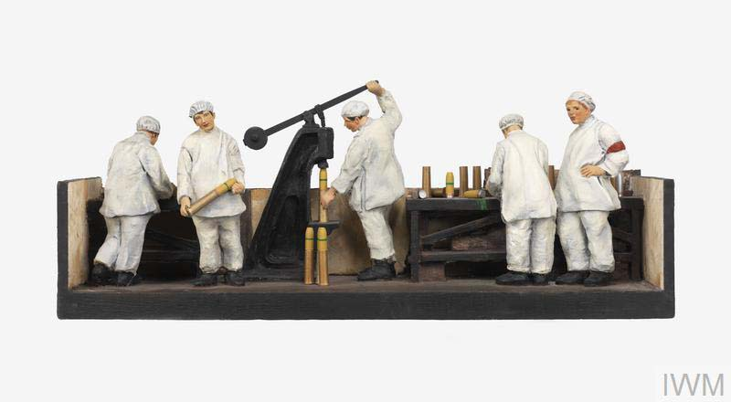 a photo of a diorama model showing white clad women filling artillery shells