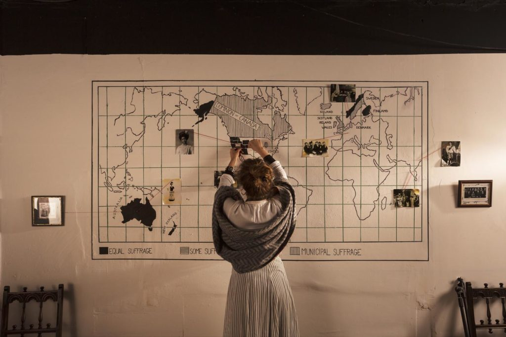 a photo of a woman in Edwardian dress adjusting a map