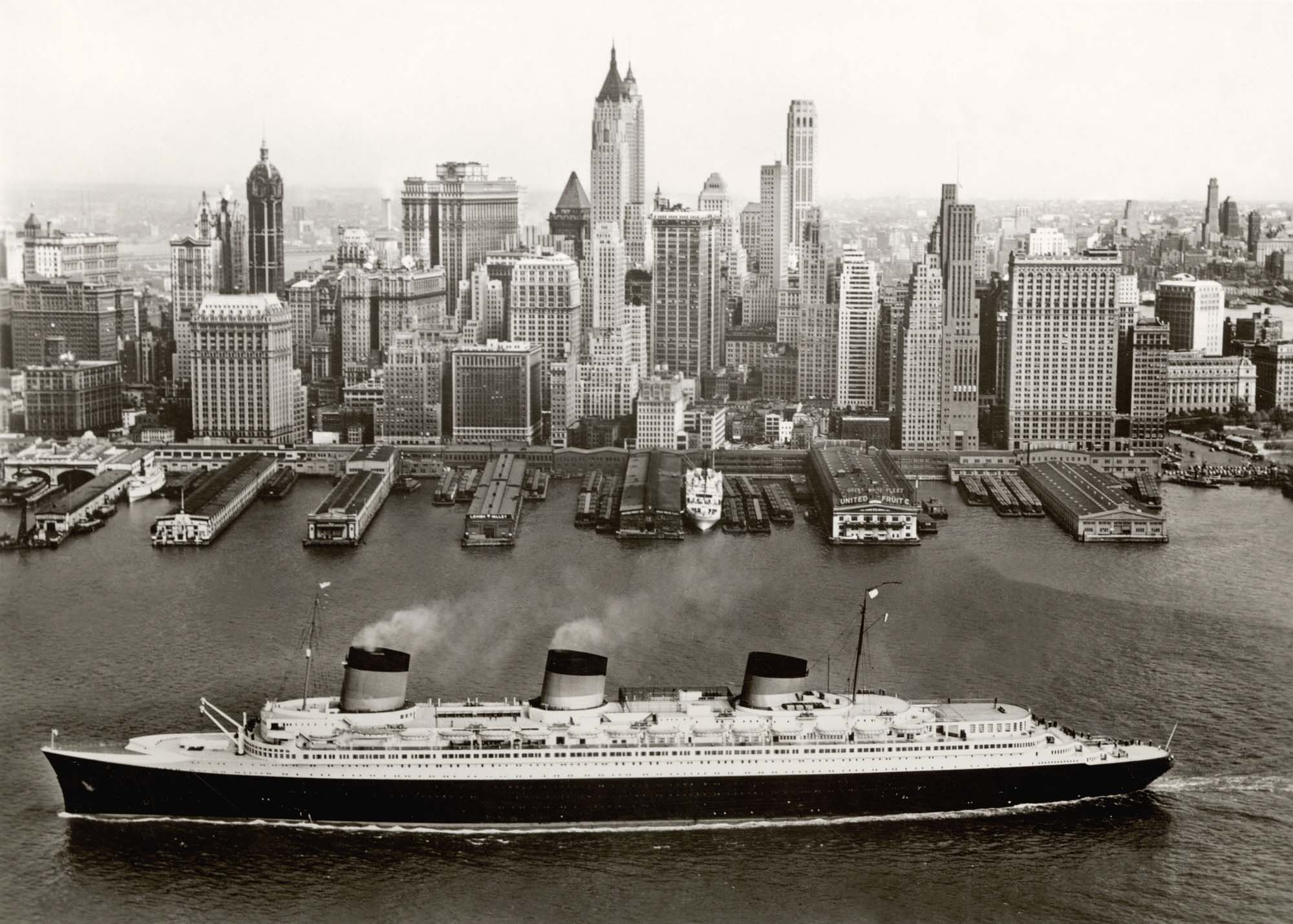 a black and white photo of a large Ocean liner in New York docks