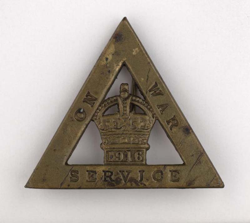 a photo of a triangular badge with the words On War Service