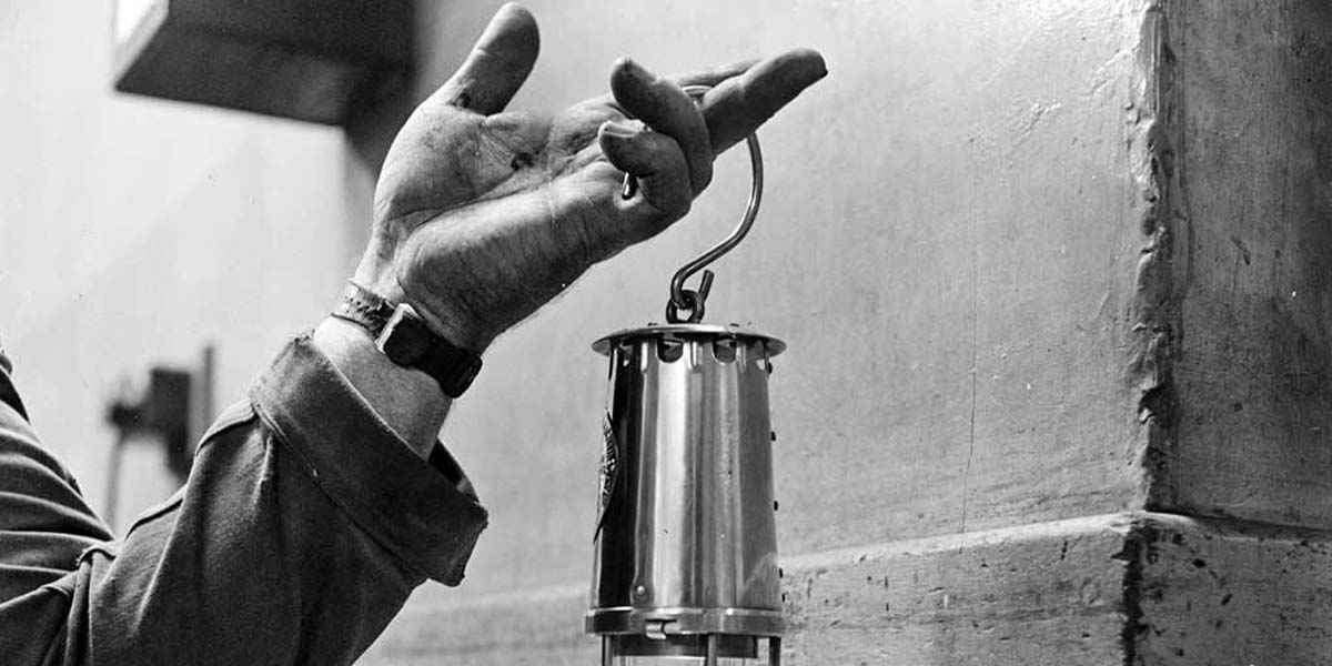 a photo of a hand holding a miners lamp held by its handle