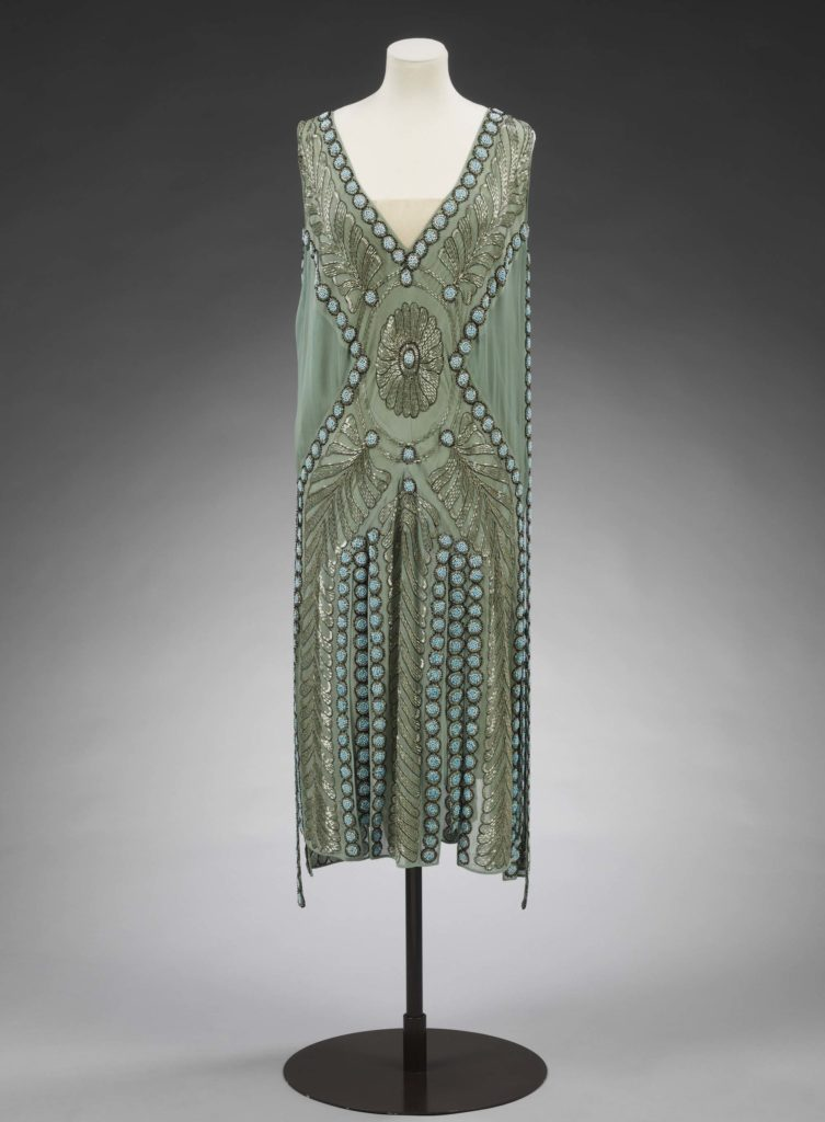 a photo of a green beaded dress on a mannequin