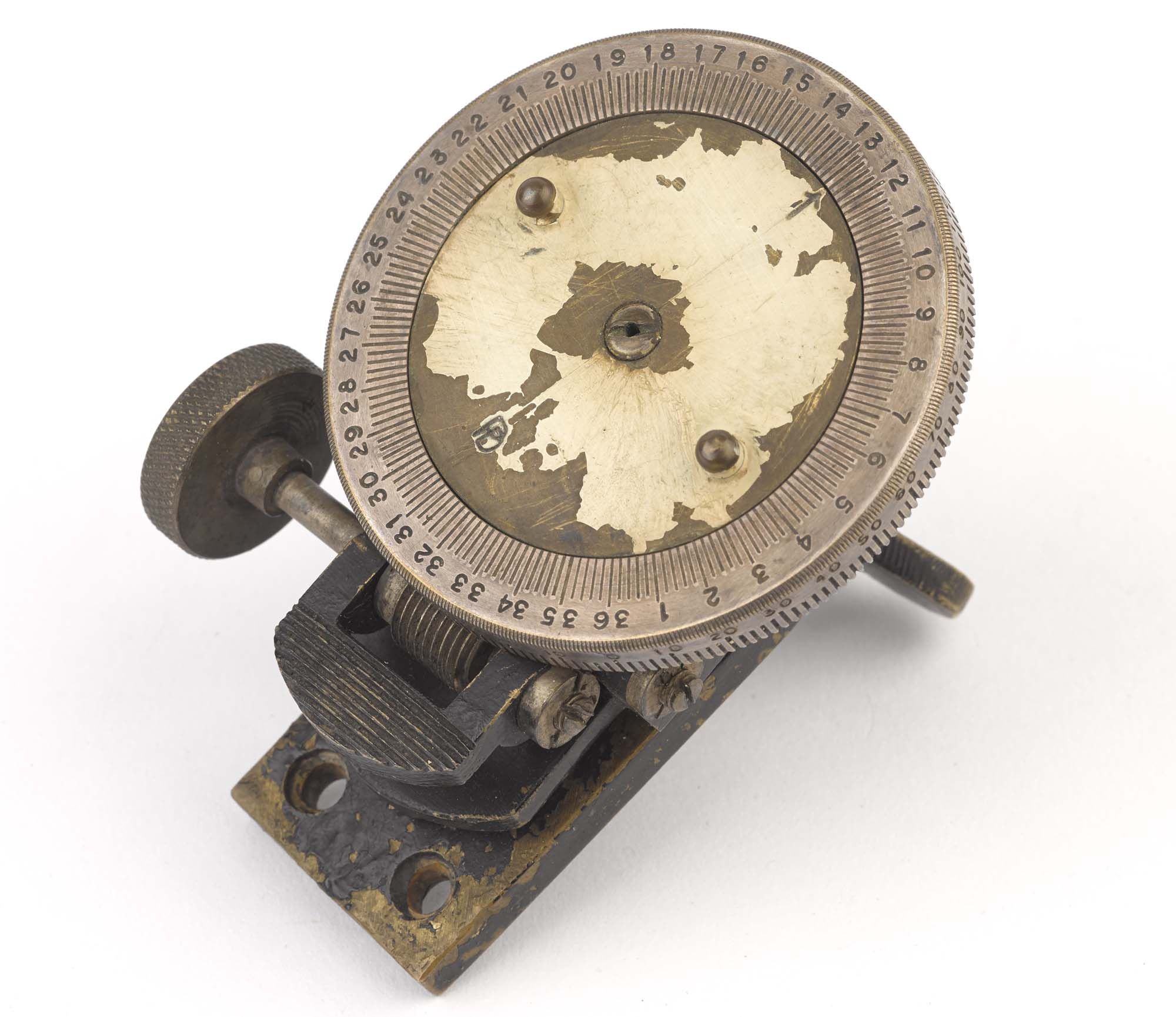 a photo of a compass made from a brass wheel on a metal stand