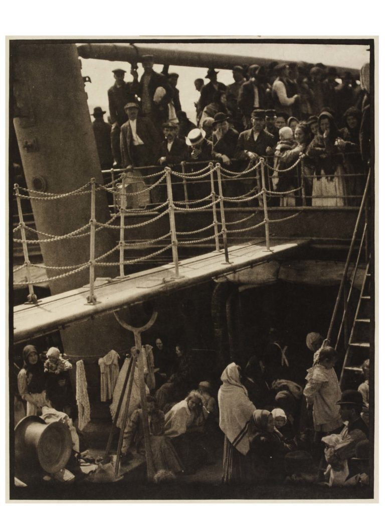 a black and white photo of passengers boarding a ship via a gang plank