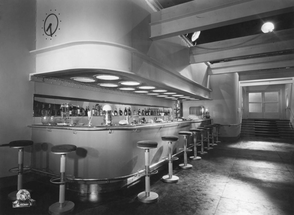a film still of a curved bar with bar stools and exposed beams