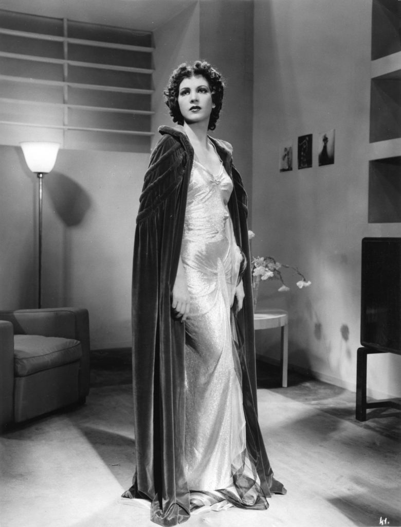 a photo of a woman in a long shimmering ball gown and cloak inside an apartment
