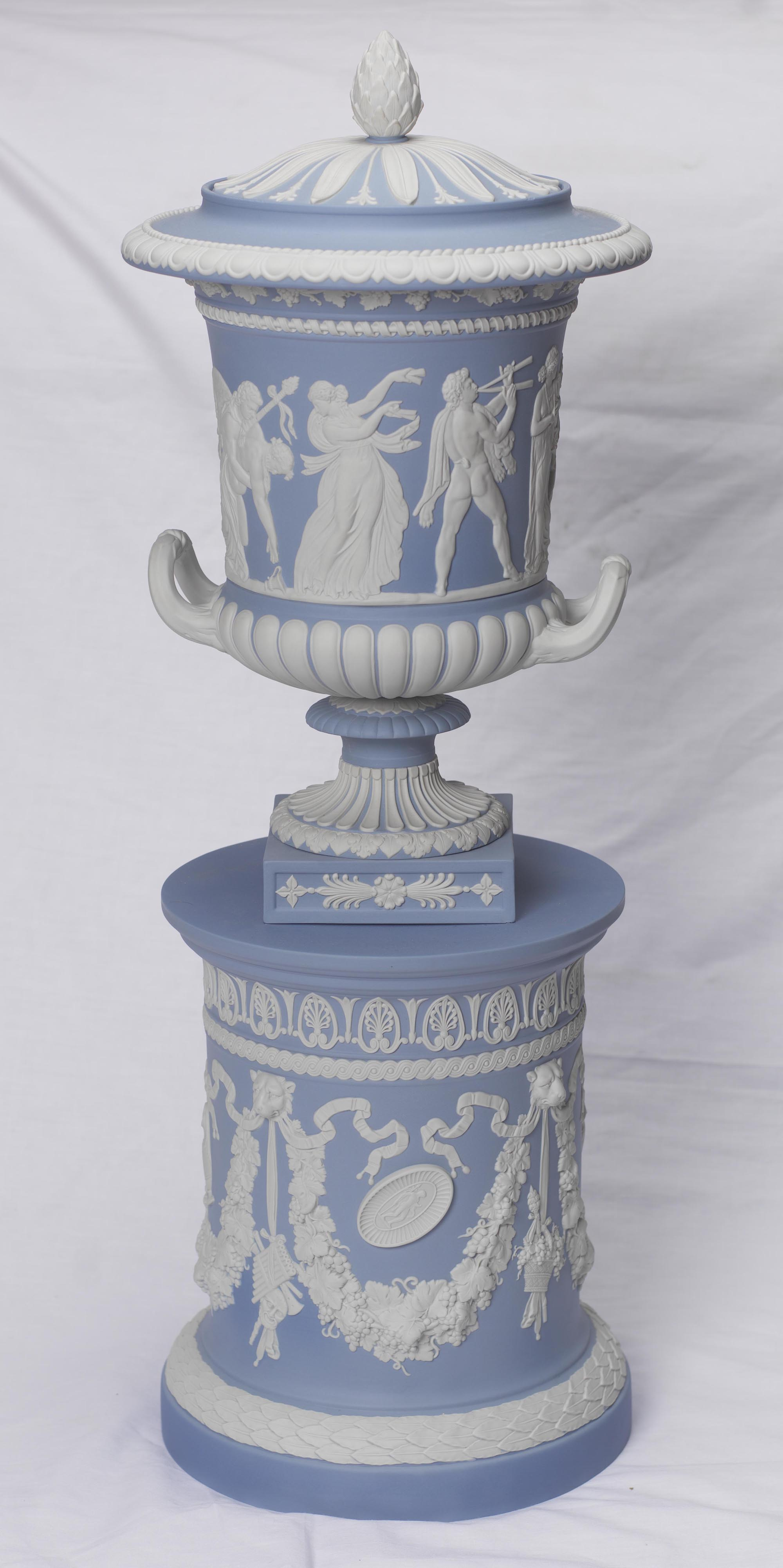 a photo of a blue urn decorated with classical figures in relief