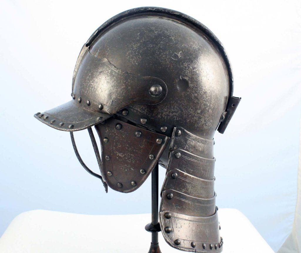 a side view of a steel helmet with neck and ear guards, peak and protective visor