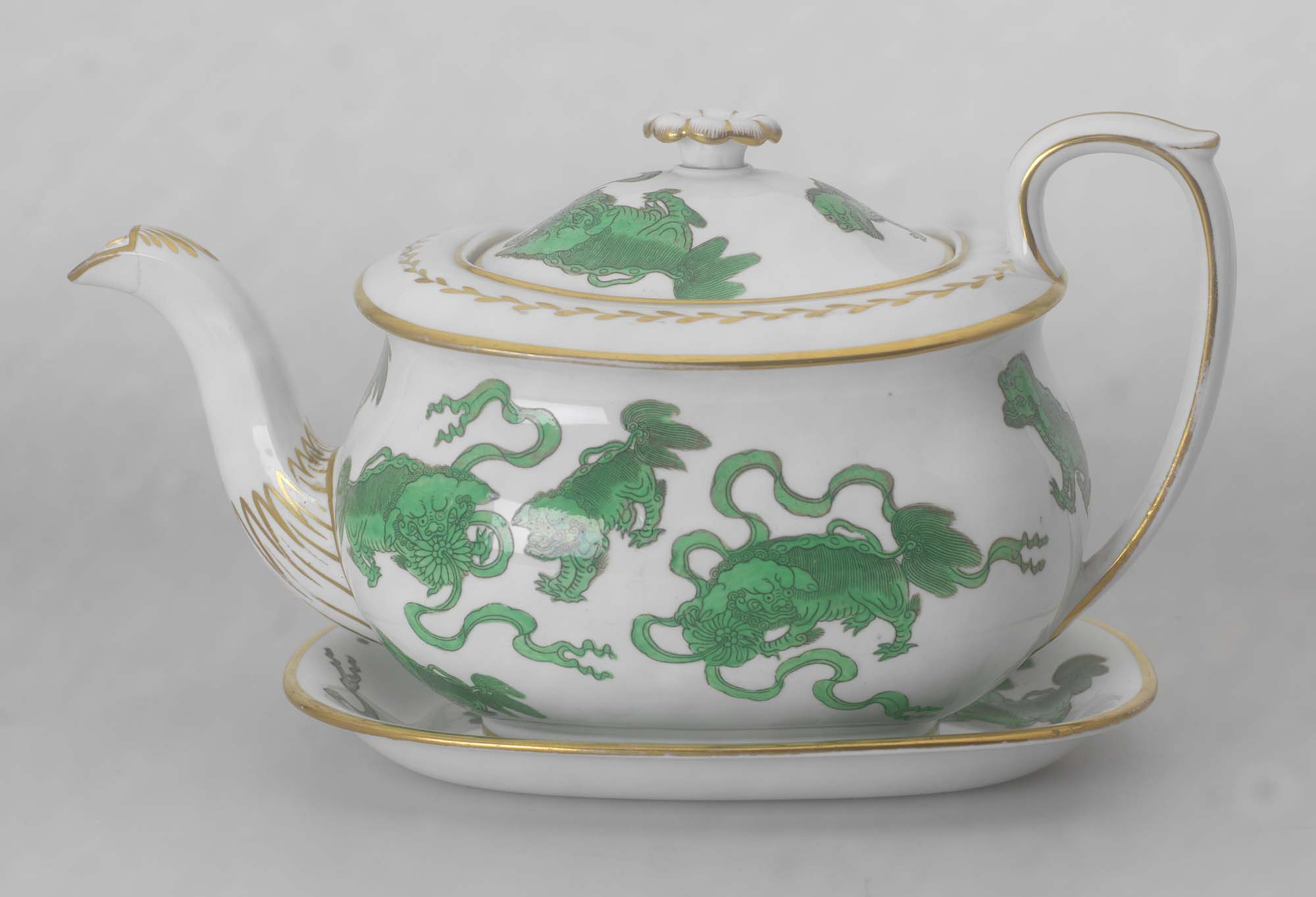 a photo of a porcelain teapot with green Chinese styled decoration