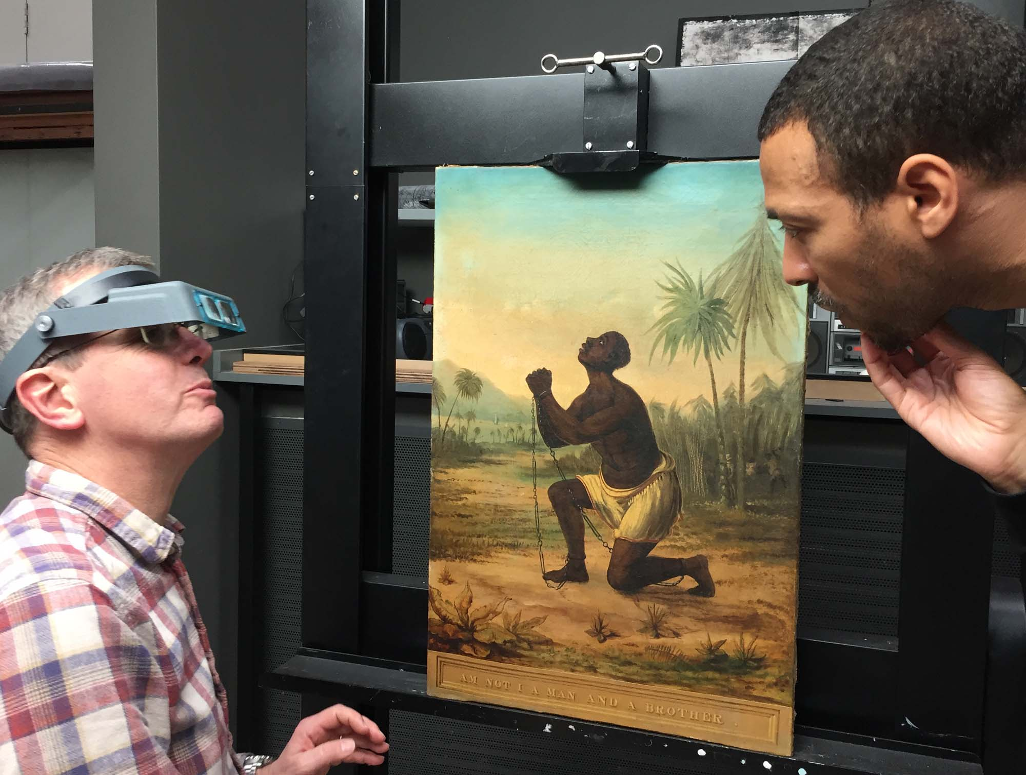 a photo of two men looking at a painting of an African slave