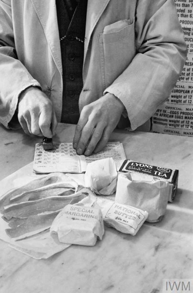 a photo of a shop counter with food and the hands of a shopkeeper stamping a ration book