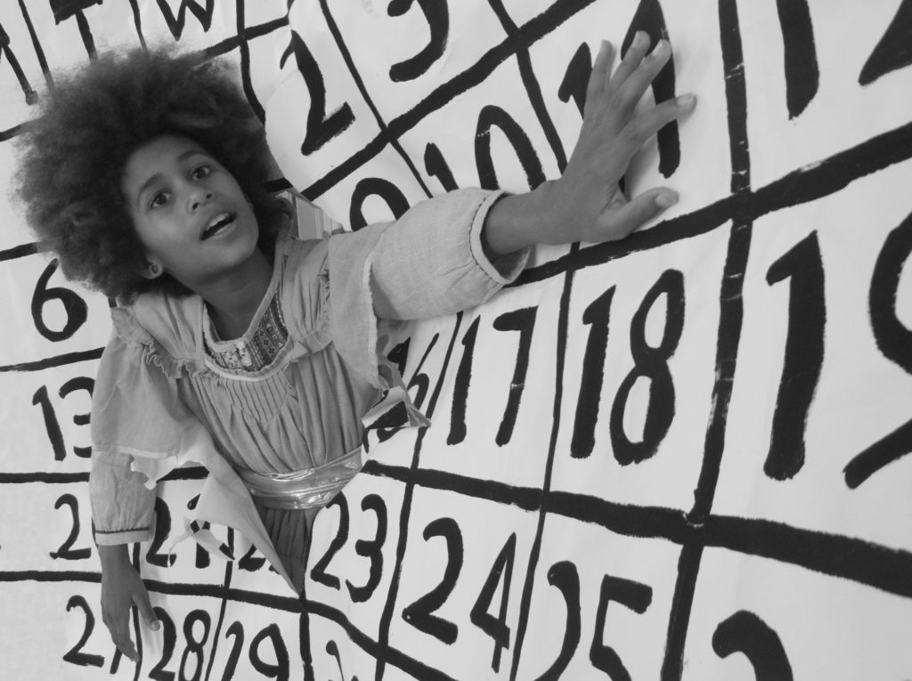 photograph of young girl breaking through an oversized hand-drawn calendar