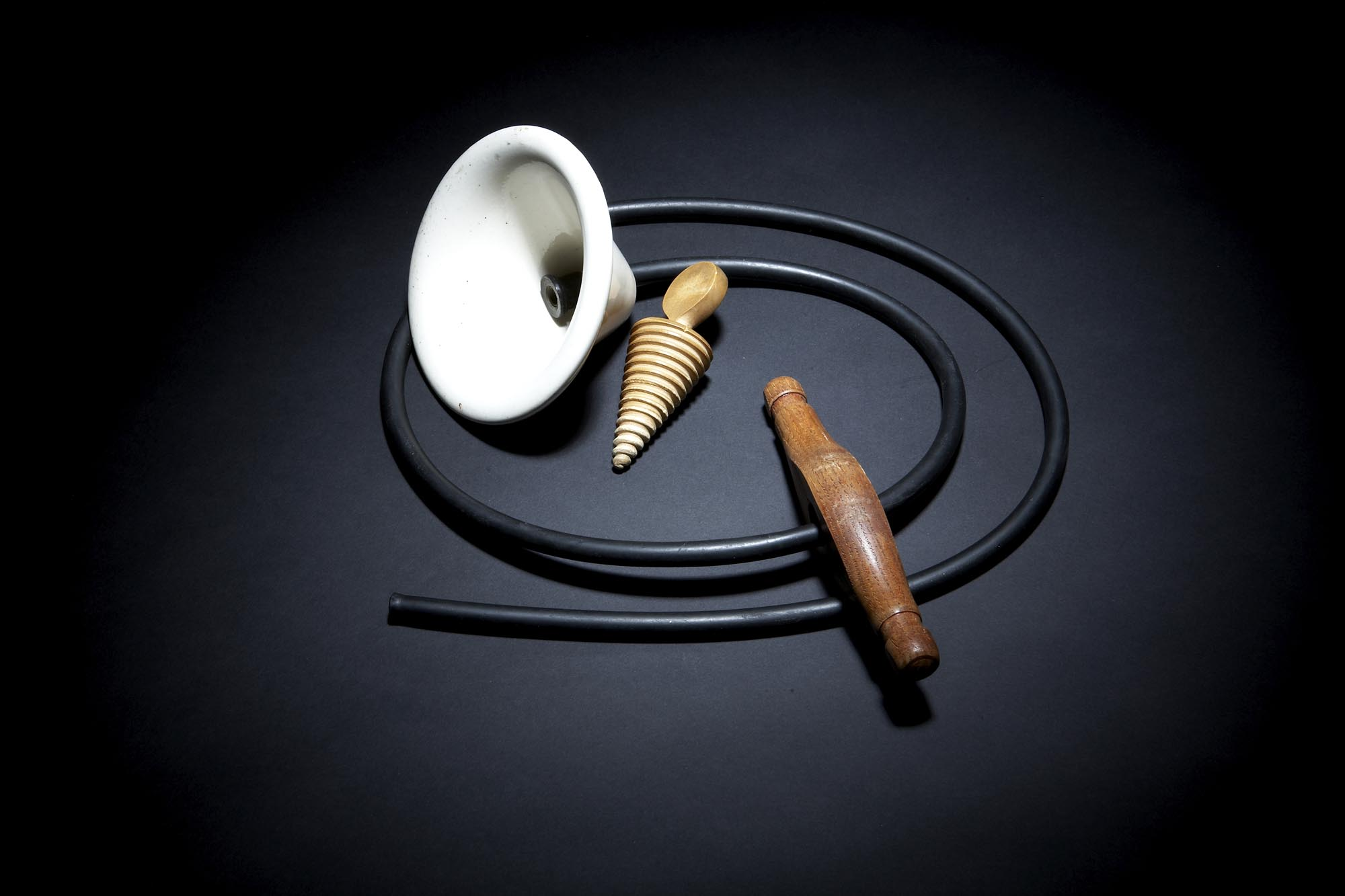 a photo of a white ceramic funnel, rubber hose and two wooden plugs