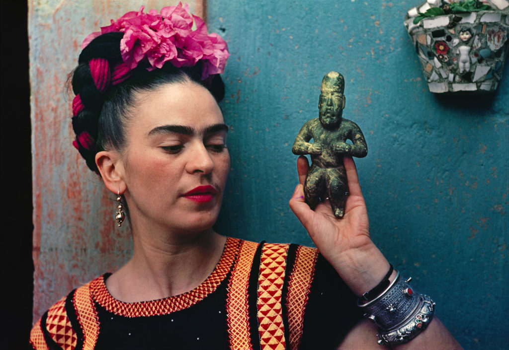 photograph of Frida Kahlo holding figurine, with pink flowers in her hair