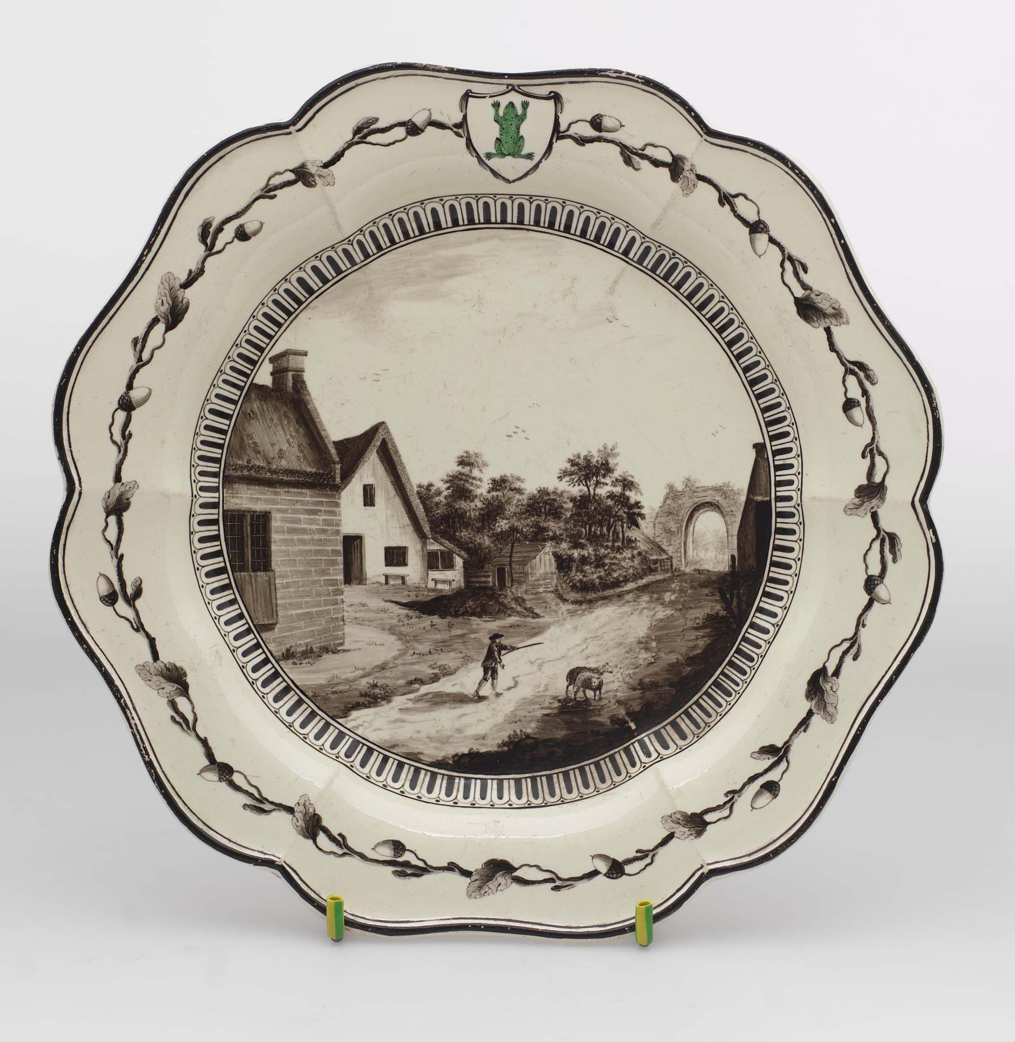a photo of a dienner plate with a rural cottage scene painted to its centre