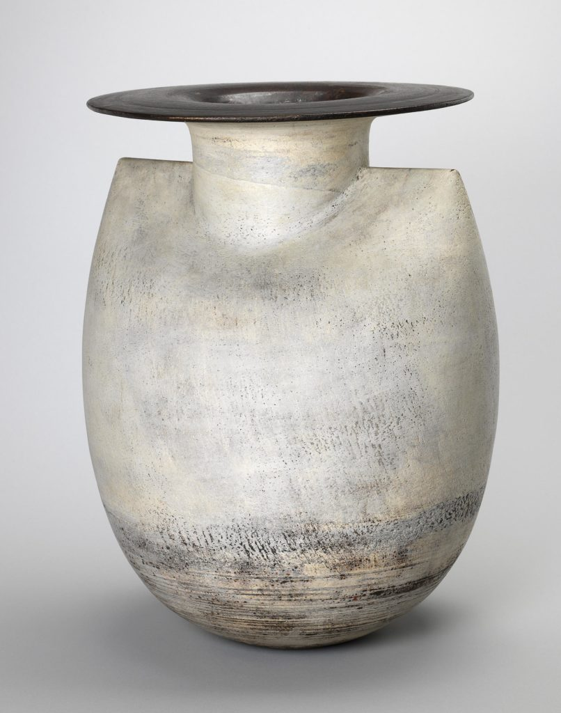 Vase with disc-shaped rim. Of swelling inverted ovoid form with shoulders at the top, cylindrical neck, and wide, flat rim.