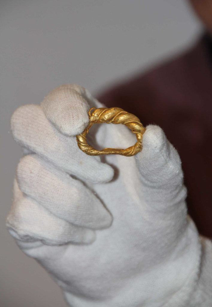 a photo of a white gloved hand holding a weighty gold ring with twisting and wire beading