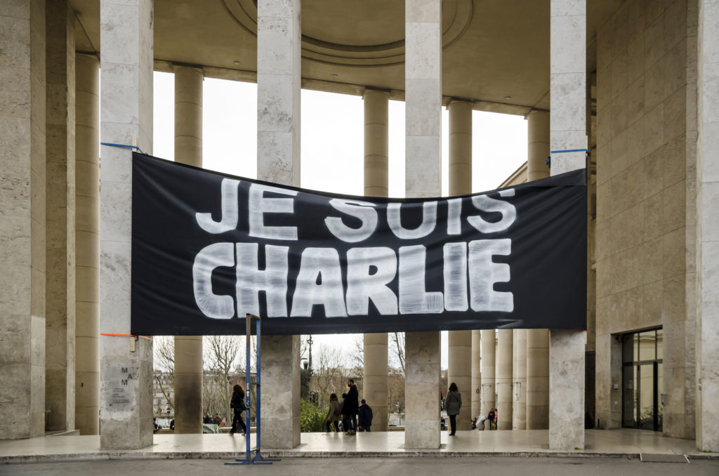 photograph of large black banner with 'je suis charlie' hand written in white suspended on large stone pillars outside a building