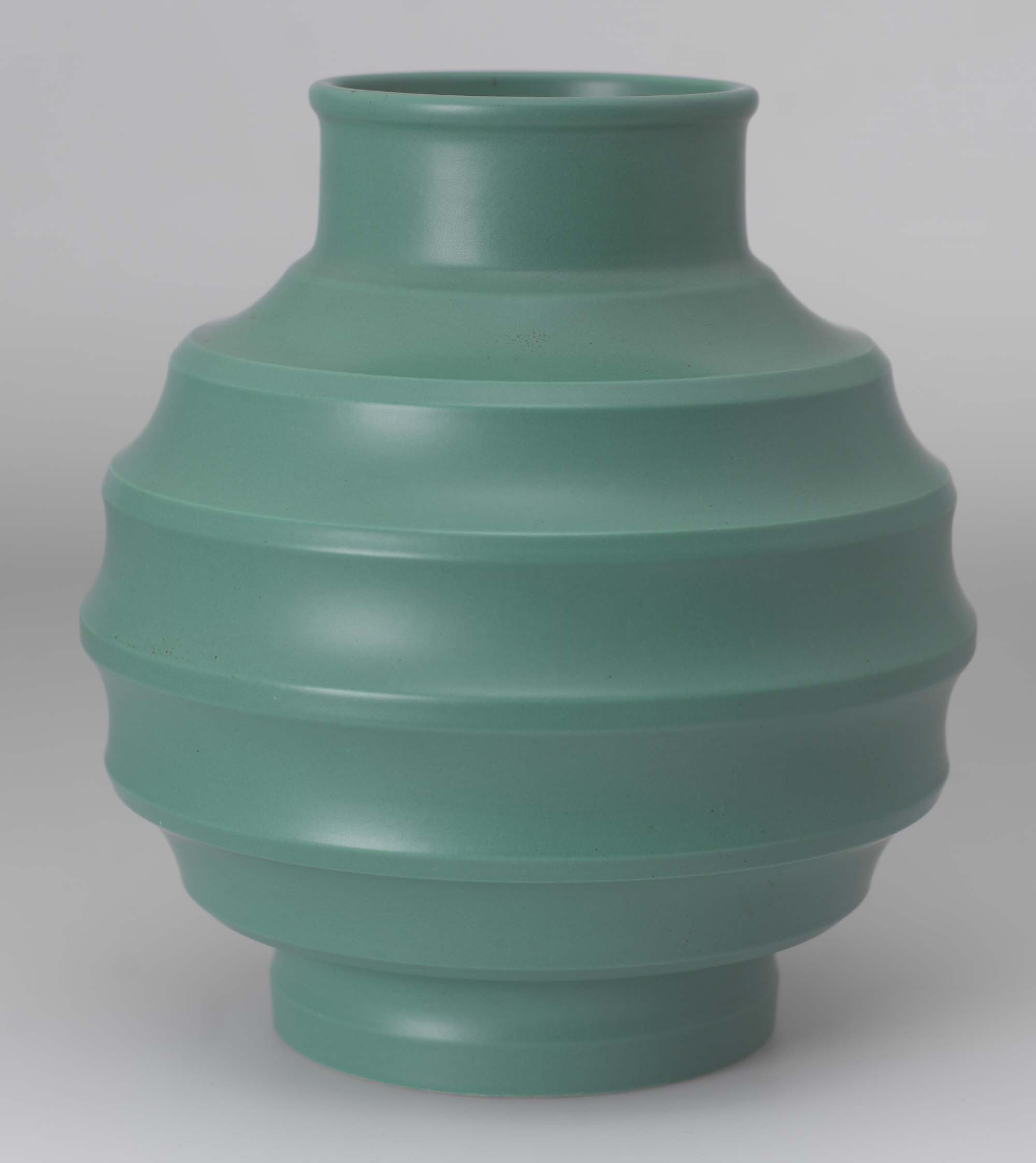a photo of a green ribbed vase