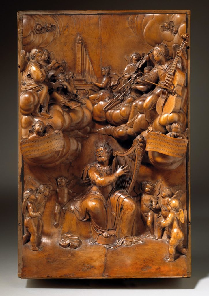 carved wooden panel depicting a concert led by King David, playing a harp and ringed by dancing cherubs