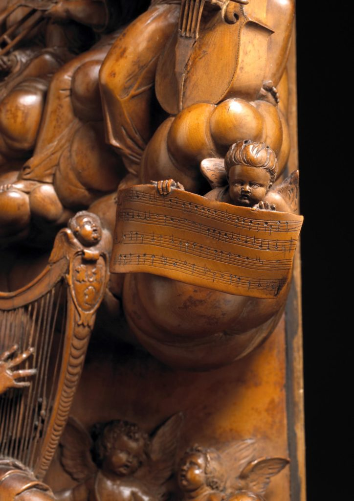 wooden carved panel, close up of a cherub holding sheet music