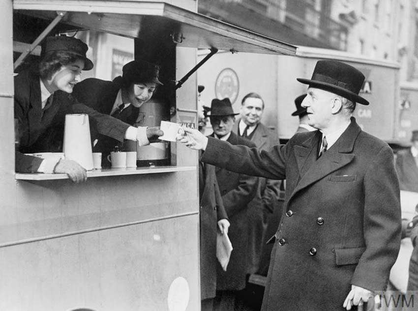 a black and white photo of a man in a homburg hat and overcoat accepting a cup of tea from a mobile canteen
