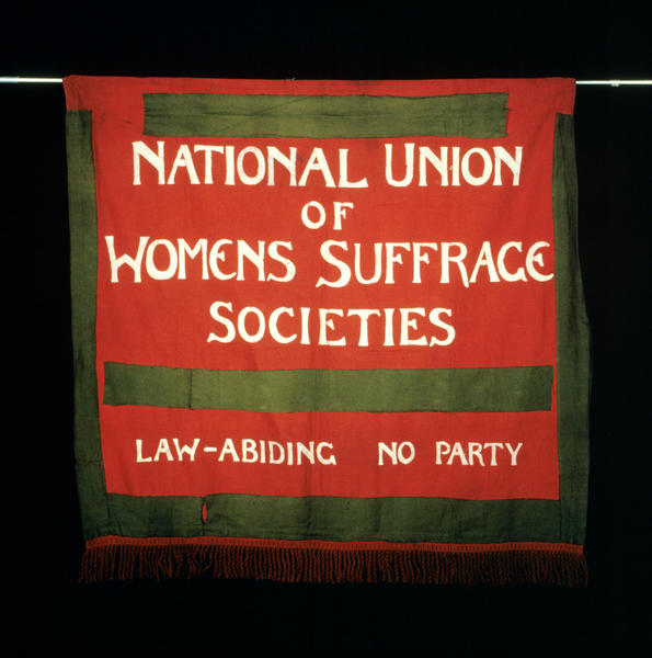 photograph of square red banner with white painted writing reading 'National Union of Womens Suffrage Societies - Law-Abiding - No Party'
