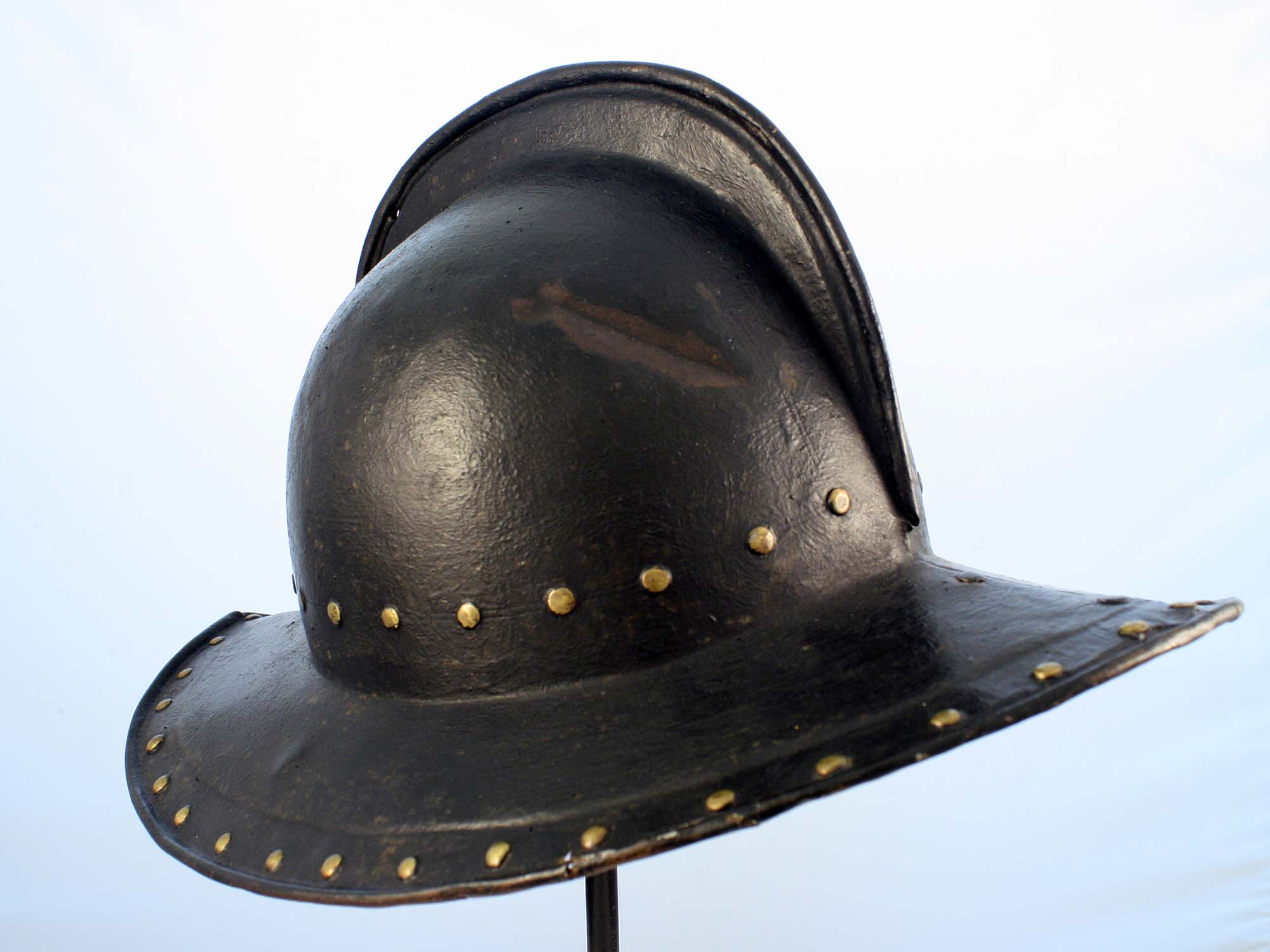 a photo of a large steel helmet with flared brim and various marks on it