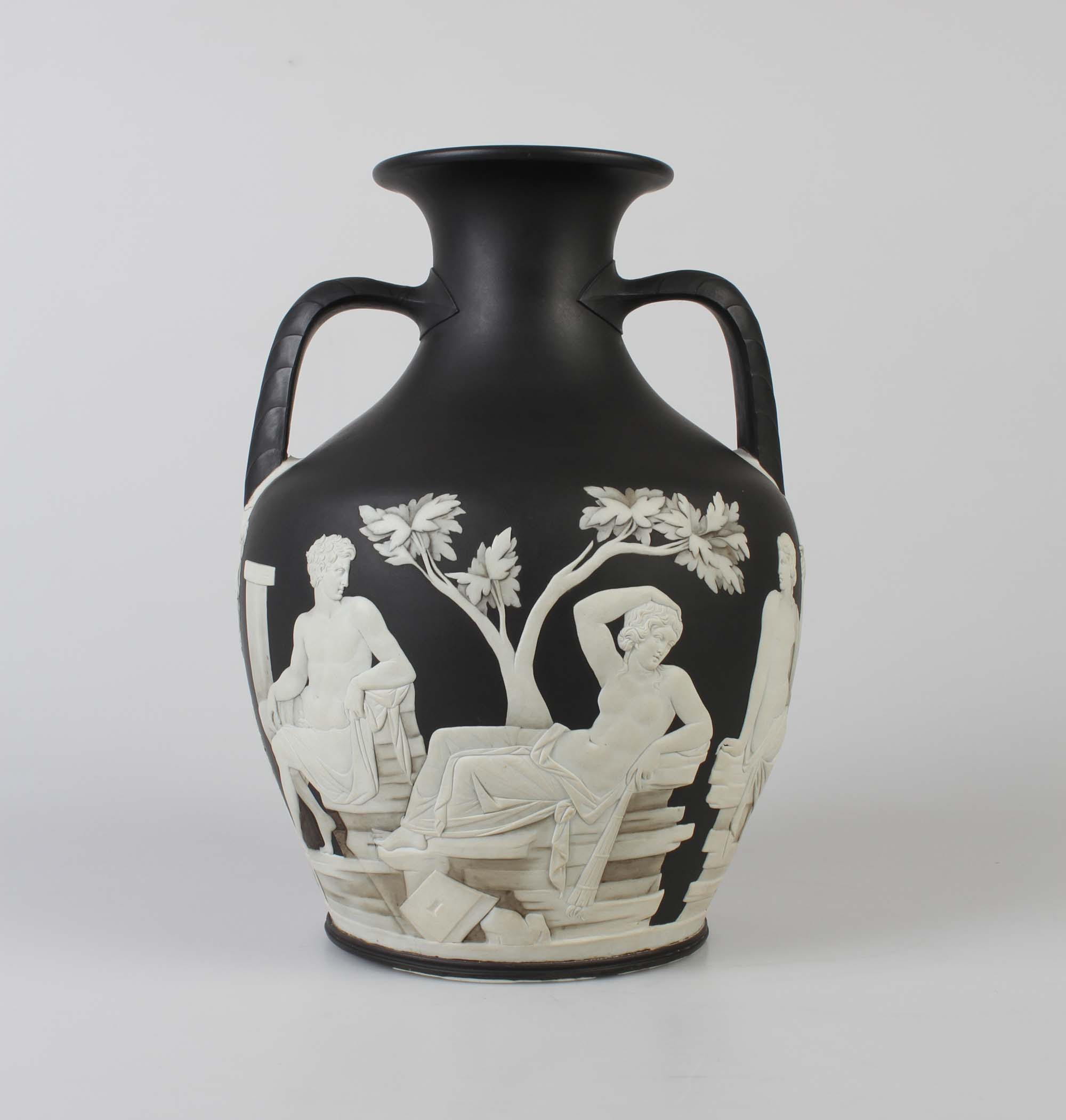 a photo of a black two handled vase with relief decoration in cream of reclining classical figures