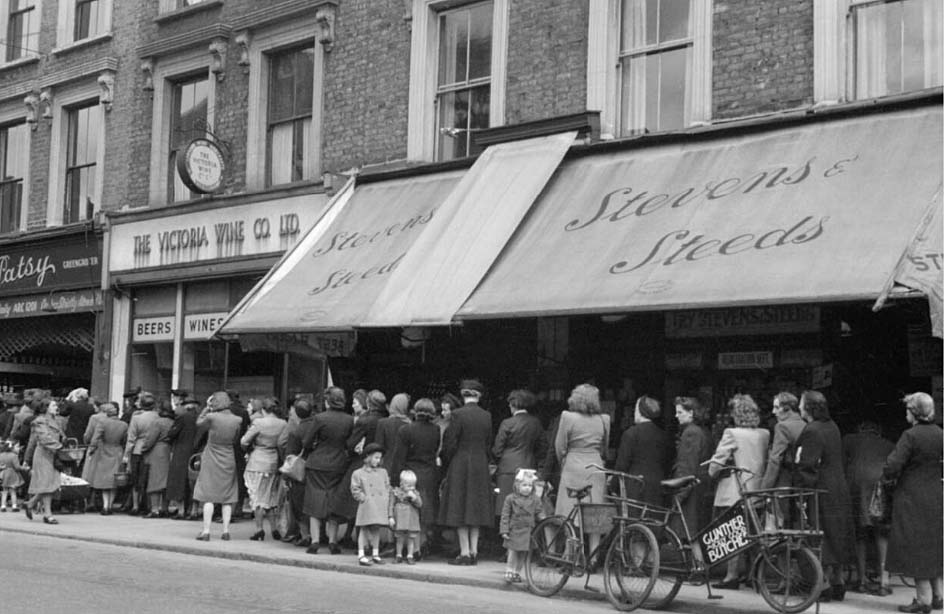 a black and white photo of women and children queuing on a street